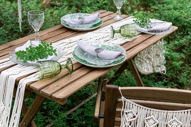 Tavolo da pranzo di ricevimento di nozze di stile di boho con la tovaglia del macramè, decorazione su una tavola di legno rustica