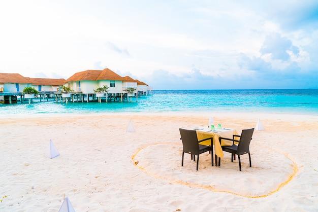 Tavolo da pranzo e sedia sulla spiaggia con sfondo vista mare alle maldive
