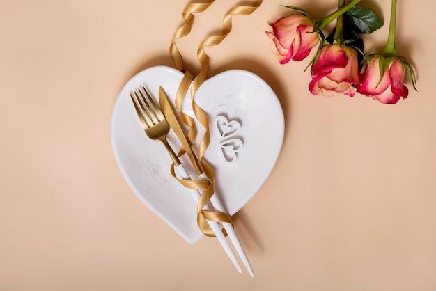 Tavolo da pranzo romantico con rose, piatto a forma di cuore e nastro dorato, san valentino o cena romantica