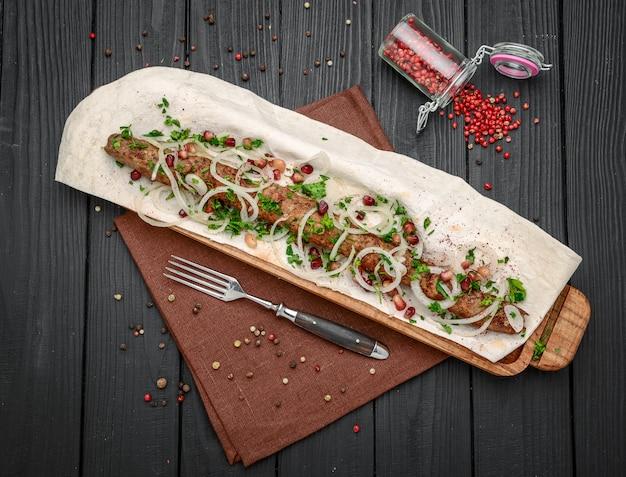 Tavolo da pranzo servito con spiedini di lula e verdure fresche. kebab in stile armeno.