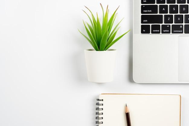 Tavolo da scrivania bianco dello spazio di lavoro dell'ufficio con il computer portatile, la matita, il taccuino e la piccola pianta. vista dall'alto con spazio di copia, piatto disteso.