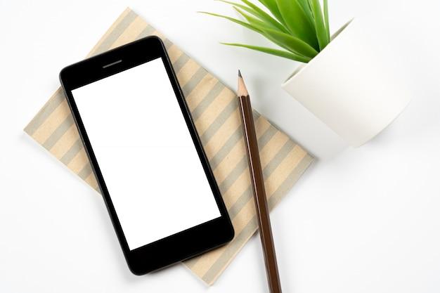 Tavolo da scrivania bianco dello spazio di lavoro dell'ufficio con lo smartphone mobile dello schermo bianco in bianco con il taccuino, matita, piccola pianta. vista dall'alto con spazio di copia, piatto disteso.
