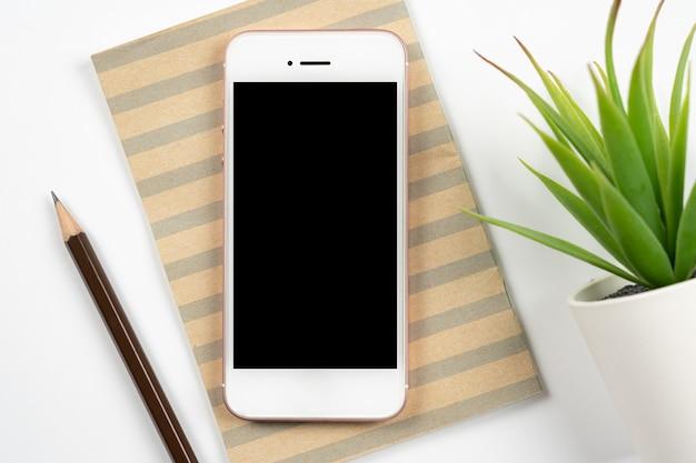Tavolo da scrivania bianco dello spazio di lavoro dell'ufficio con lo smartphone mobile dello schermo nero in bianco con il taccuino, matita, piccola pianta. vista dall'alto con spazio di copia, piatto disteso.