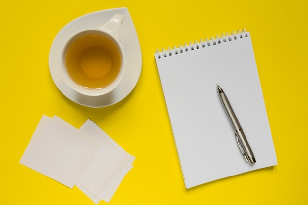 Tavolo da scrivania giallo in stile da ufficio con taccuino, computer, forniture e tee cup.