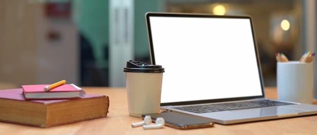 Tavolo da studio con libri, laptop, smartphone, auricolari, articoli di cancelleria e bicchiere di carta