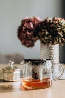 Tavolo da tè in vetro con fiori all'interno della casa