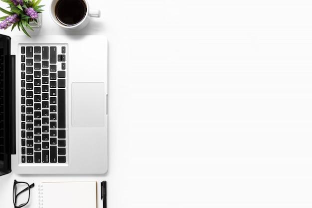 Tavolo da ufficio bianco con computer portatile, tazza di caffè e forniture per ufficio.
