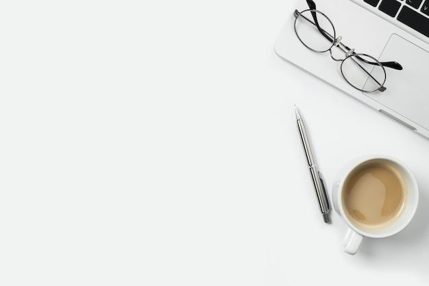 Tavolo da ufficio bianco con computer portatile, tazza di caffè e forniture.