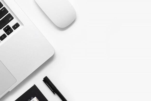 Tavolo da ufficio bianco con laptop e forniture per ufficio.