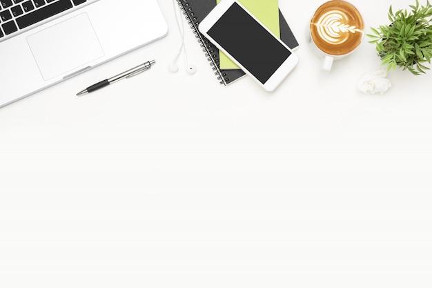 Tavolo da ufficio bianco con laptop, smartphone, tazza di caffè e forniture.