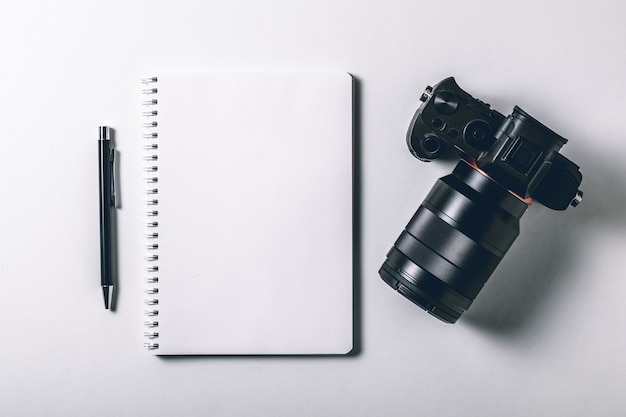 Tavolo da ufficio bianco con penna e fotocamera digitale mirrorless.