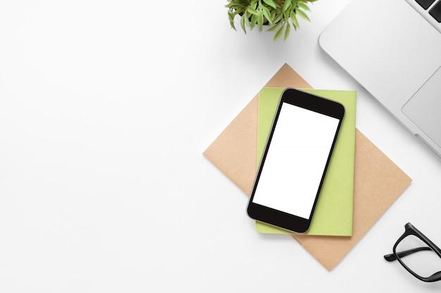Tavolo da ufficio bianco con smartphone con schermo vuoto e altri articoli per ufficio.