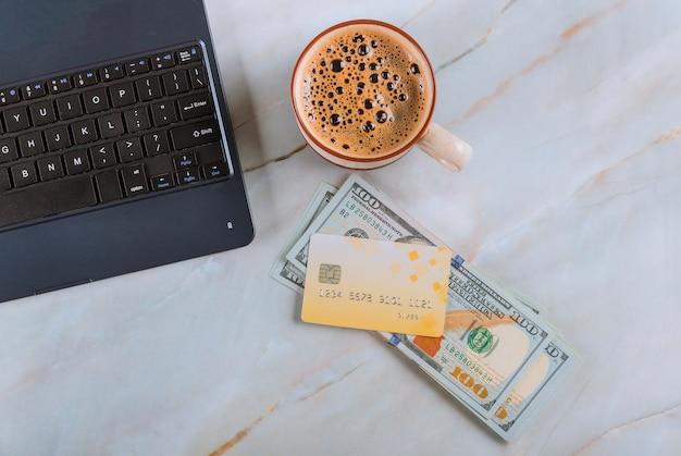 Tavolo da ufficio con banconote da cento dollari, computer con carta di credito e tazza di caffè