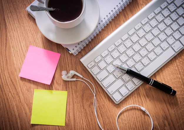 Tavolo da ufficio con blocco note, tastiera del computer, tazza di caffè, penna, cuffia, note adesive