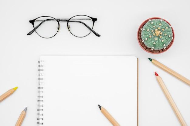 Tavolo da ufficio con cactus, quaderno, occhiali e matita