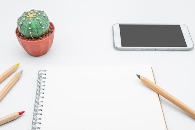 Tavolo da ufficio con cactus, smartphone, notebook e matita