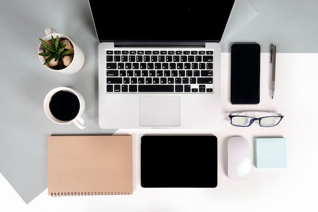 Tavolo da ufficio con computer portatile, notebook, tavoletta digitale e telefono cellulare a due toni b