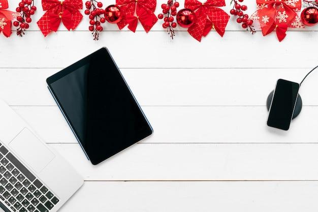 Tavolo da ufficio con dispositivi, forniture e decorazioni natalizie. vista dall'alto