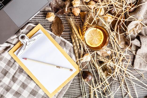 Tavolo da ufficio con laptop, forniture, tazza di tè nero al limone, physalis, castagne