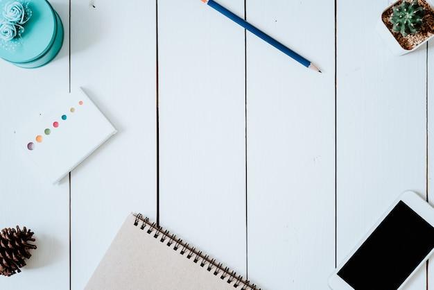 Tavolo da ufficio con taccuino, smart phone, penna, bigliettini e cactus. vista dall'alto con copyspace