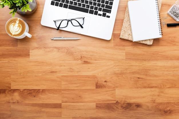 Tavolo da ufficio in legno con computer portatile, tazza di caffè e forniture.