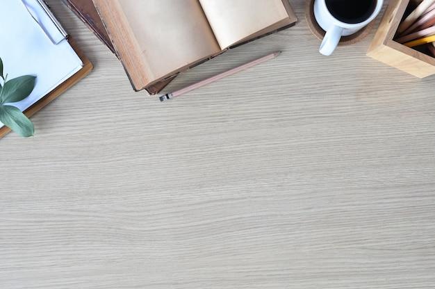 Tavolo da ufficio in legno con libri, cartoncino, caffè e matita.