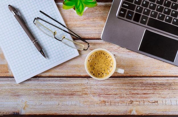 Tavolo da ufficio in legno con penna per occhiali laptop e cuffie