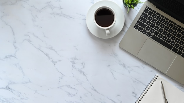 Tavolo da ufficio in marmo con laptop, penna, quaderno e caffè con pianta, area di lavoro business laica piatta.