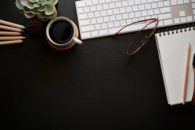 Tavolo da ufficio in pelle scura con computer desktop, quaderno aperto, tazza da caffè