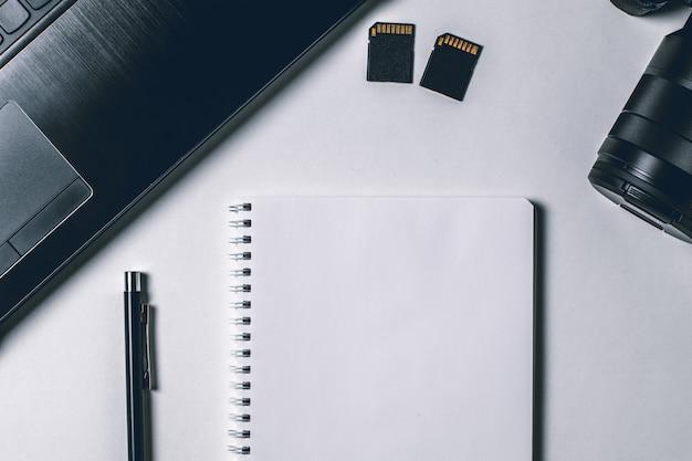 Tavolo da ufficio moderno bianco con laptop, fotocamera e altri materiali di consumo. pagina del taccuino vuoto per inserire il testo nel mezzo. vista dall'alto, piatta distesa.