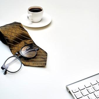 Tavolo da ufficio moderno bianco con una tazza di caffè, cravatta e altre forniture.