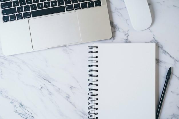 Tavolo da ufficio moderno in marmo con laptop e altri accessori. pagina di quaderno bianco vuoto per testo di input o breve nota di inserimento, copia spazio per contenuti creativi, pubblicità e design. vista dall'alto, piatto.
