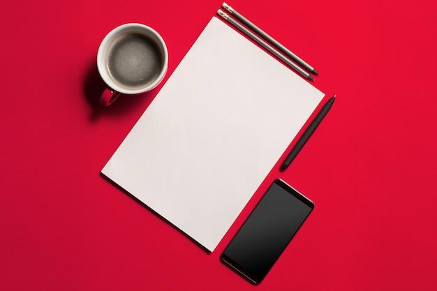 Tavolo da ufficio moderno rosso con smartphone e tazza di caffè.