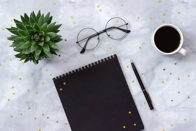 Tavolo da ufficio o da casa. blocco note nero, penna, tazza di caffè, succulente su fondo di marmo