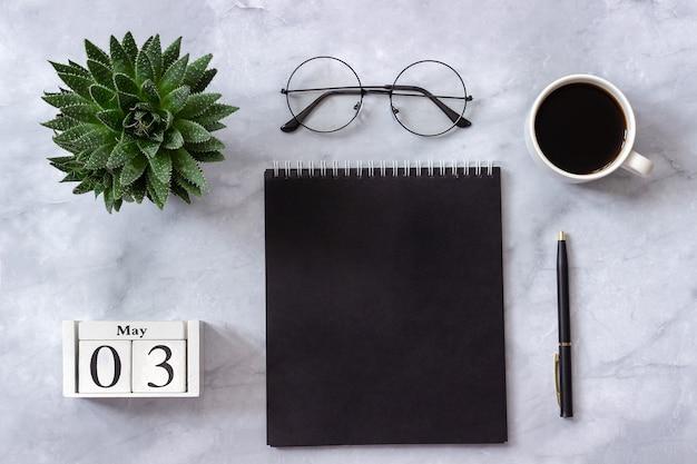 Tavolo da ufficio o da casa. calendario 3 maggio. blocchetto per appunti nero, caffè, succulente, vetri su fondo di marmo