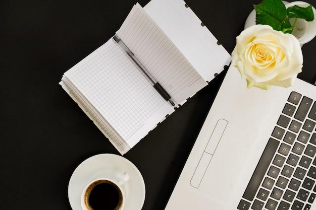 Tavolo da ufficio piatto con vista dall'alto. area di lavoro con laptop, rosa bianca, diario aperto e tazza di caffè su sfondo nero.