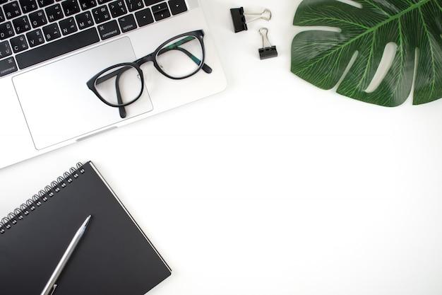Tavolo da ufficio piatto con vista dall'alto. l'area di lavoro ha un computer portatile, un taccuino, una penna, una lavagna per appunti, occhiali e foglie con un'area di copia.