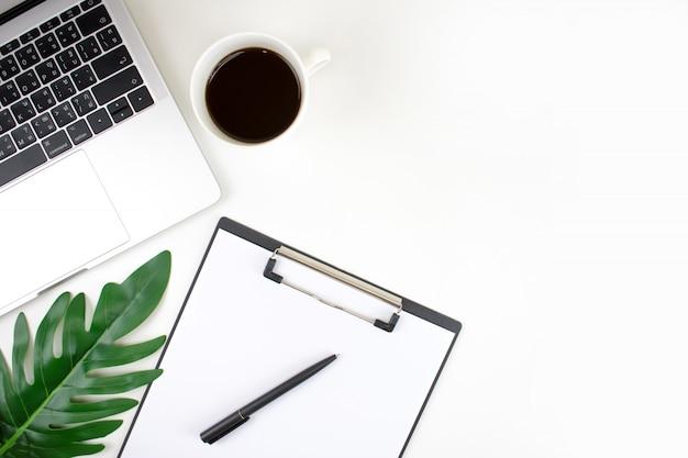 Tavolo da ufficio, vista dall'alto con laptop, foglia di palma, taccuino e accessori. copia spazio.