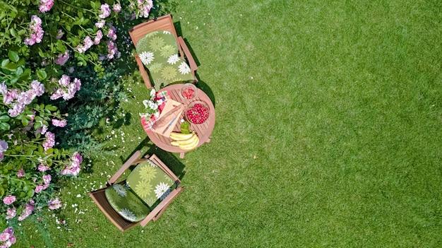 Tavolo decorato con pane, fragole e frutta nel bellissimo roseto estivo, vista dall'alto aerea della romantica data tabella cibo impostazione per due dall'alto