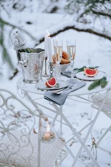 Tavolo decorato per una cena romantica con candele, spumante e frutta nella foresta invernale