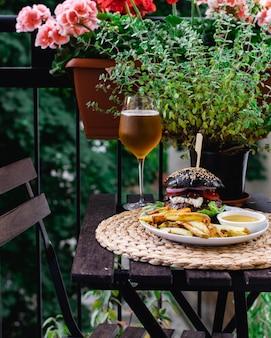 Tavolo del ristorante sulla terrazza con hamburger dal panino nero