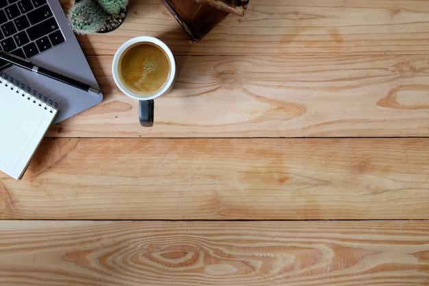 Tavolo di area di lavoro dell'ufficio con il computer portatile, il taccuino e stazionario sullo scrittorio di legno marrone.