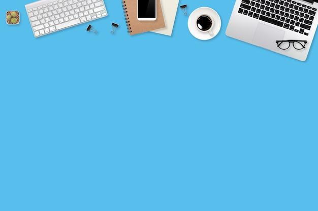 Tavolo di lavoro con computer portatile, articoli per ufficio, cellulare e tazza di caffè su sfondo blu pastello