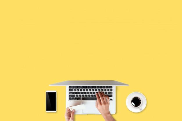Tavolo di lavoro di tecnologia con le mani della donna sul computer portatile, carta di credito, tazza di caffè e telefono cellulare su giallo (o concetto online di acquisto e pagamento)