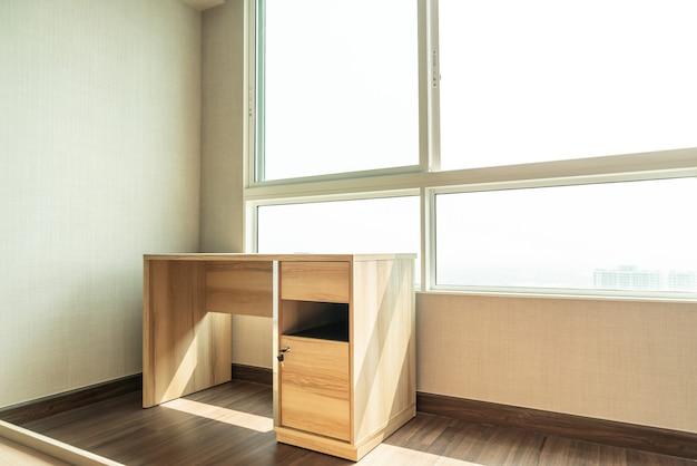 Tavolo di lavoro vuoto in camera con finestra