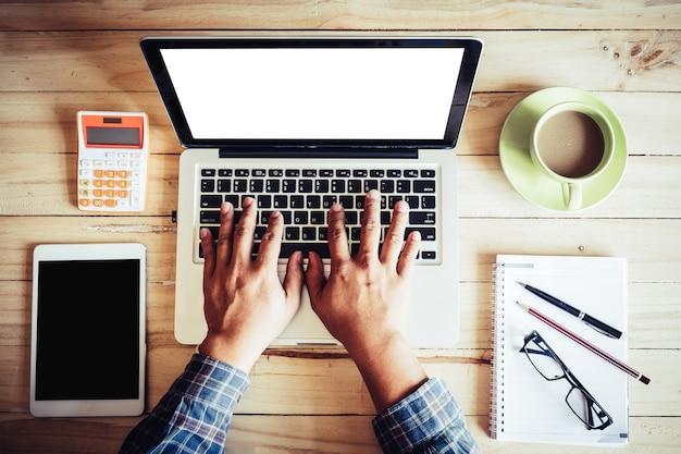 Tavolo di legno da ufficio con le mani dell'uomo su computer portatile modello, calcolatrice, tavoletta, tazza di caffè e occhiali da vista, penna a matita sul notebook