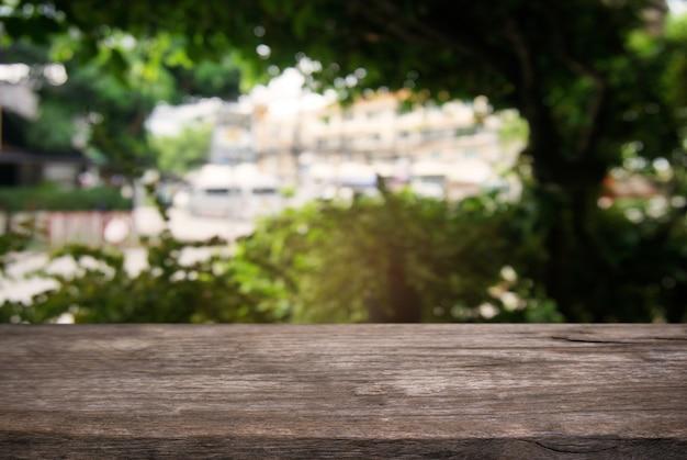 Tavolo di legno scuro vuoto davanti astratto sfondo sfocato di caffè e caffè interno. può essere utilizzato per visualizzare o montare i tuoi prodotti.