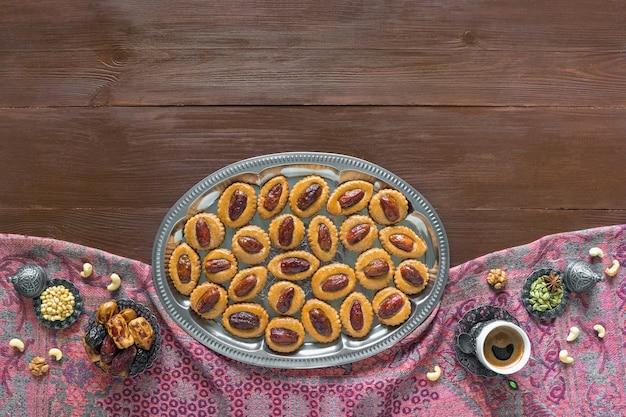Tavolo dolce festivo del ramadan con i biscotti casalinghi della data su una tavola di legno marrone