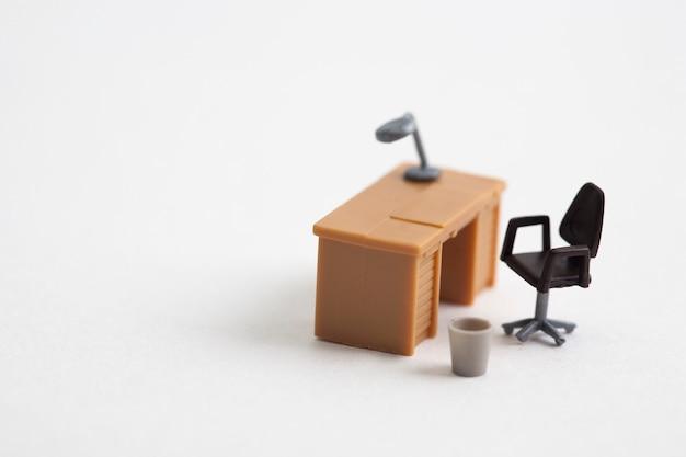 Tavolo e sedia in miniatura su sfondo bianco