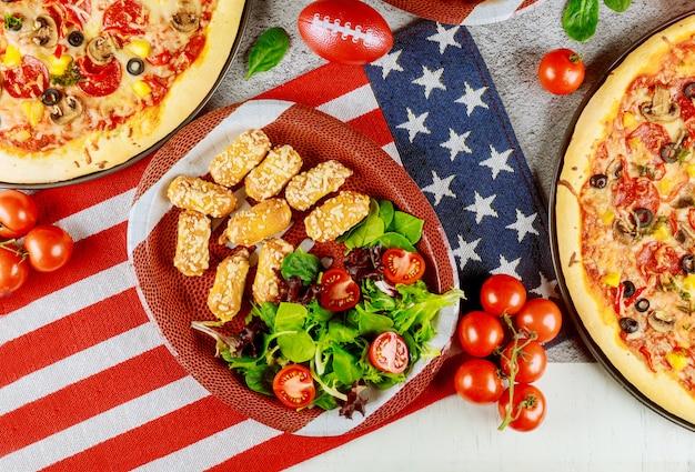 Tavolo festivo con patate fritte, pizza e verdure per le vacanze americane